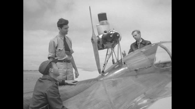 Harry Perl Don Mitchell and designer Ted Nelson stand around the streamlined fuselage of the Hummingbird and discuss the engine perched atop the...