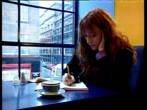 vídeos de stock e filmes b-roll de 'harry potter' author jk rowling writing at coffee table and looking through window; 2000 - literatura