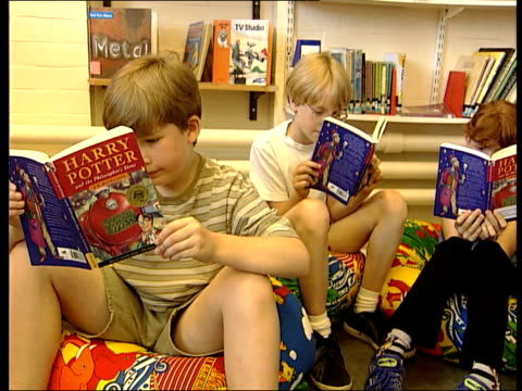 harry potter books phenomenon; england: london: int cms & child reading from harry potter book 'harry potter and the philosopher's stone' by j.k.... - harry potter titolo d'opera famosa video stock e b–roll