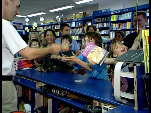 London Queue of children in bookshop counting down seconds until time when the new 'Harry Potter' book goes on sale SOT MS Children holding out hands...