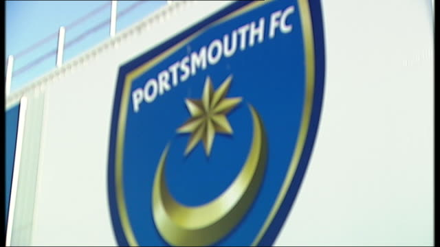Redknapp cleared of tax fraud 2312012 Portsmouth FC badge on side of stadium Groundsman mowing pitch Fratton Park entrance and sign