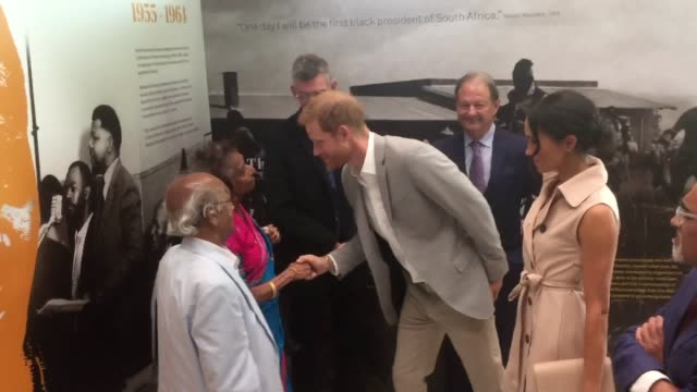 Harry shakes hand of Nelson Mandela's friend and political ally Paul Joseph and his wife Adelaide Meghan looks into a glass cabinet at a Robben...