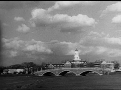 harvard university campus dunster house tower w/ weeks footbridge charles river fg male crew rowing on river w/ campus bg two male students walking... - 1951 stock-videos und b-roll-filmmaterial