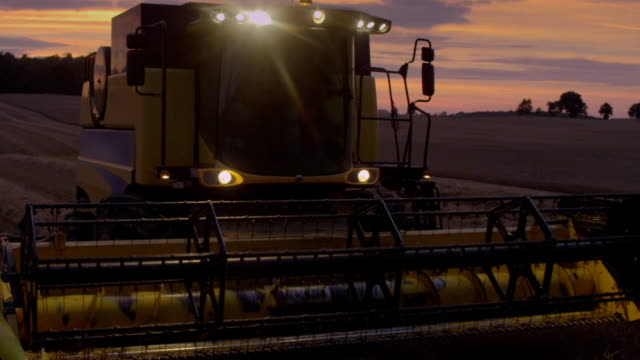 日没時に収穫します。ピンクは、不機嫌そうな空 - トラクター点の映像素材/bロール