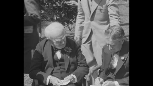 vídeos y material grabado en eventos de stock de ms harvey firestone and thomas edison sit outside in director's chairs firestone writes on notepad men writing on notepads behind them then walk away... - fort myer