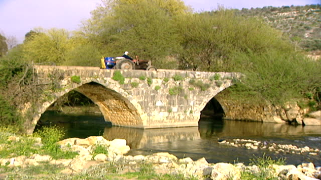 hasbani river. view of a tractor crossing an ancient roman double-arched bridge spanning the river. - rapid stock videos & royalty-free footage