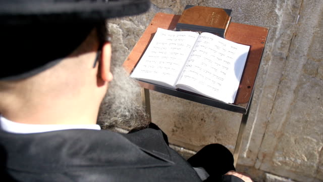 hasidic old jew praying at the wailing wall, over the shoulder view, close-up - western script stock-videos und b-roll-filmmaterial