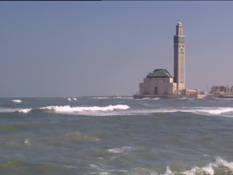 Hassan II Mosque jutting out to sea rolling waves in foreground Casablanca
