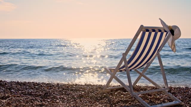slo mo hat and an empty chair on the beach - beach chairs stock videos & royalty-free footage