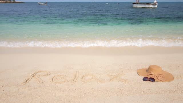 Mütze und Sonnenbrille am Strand, Meer, Sommer und Entspannung Konzept, 4 k (UHD