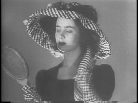 hat tree full of designer hats / woman holding hat of transparent glass straw glowing from light behind / women modelling a large black and white... - sailor hat stock videos & royalty-free footage