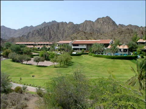 Hatta Fort hotel resort with golf course in the foreground and mountain range in the background pan right to palm trees and more of the resort.