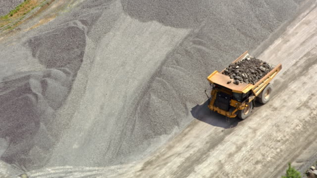AERIAL Haul trucks driving in the quarry