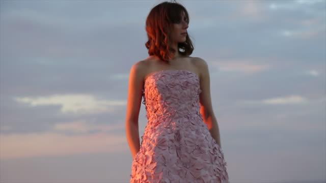 vídeos de stock e filmes b-roll de haute couture model poses against a desert backdrop, sunset - só mulheres jovens
