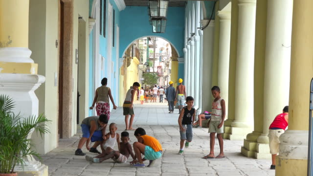 a group of cuban children plays below a colonialstyle porch while locals and tourists go out and about in the area old havana is a unesco world... - veranda stock videos & royalty-free footage