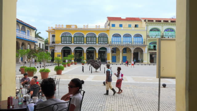 old colonial architecture buildings surrounding the famous place and tourist attraction tourists sit in an old porch drinking while locals go out and... - plaza vieja stock videos and b-roll footage
