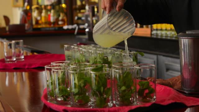 havana cuba famous nacional hotel bartender piuring mojitos in glasses at bar - hotel nacional stock videos and b-roll footage