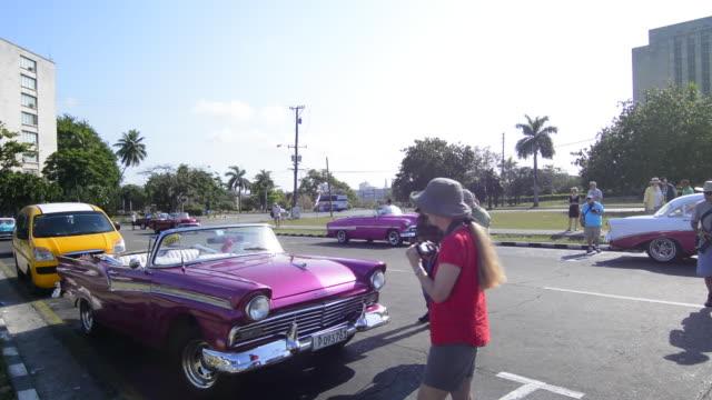 Havana Cuba Habana tourists taking photos of old cars in Revolution Square
