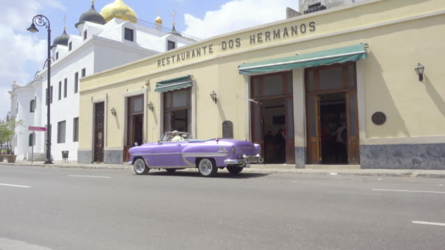 havana cuba old classic american purple car in front of a famous dos hermanos restaurant visited by hemingway and famous because of mojitos and live music. a man starts the car and drives away and another man gets into the restaurant. - music video stock videos and b-roll footage