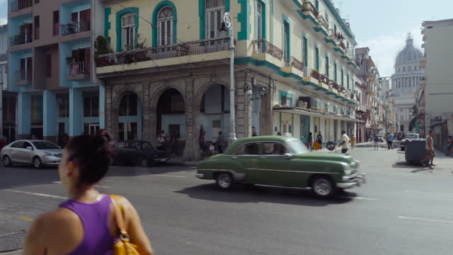 havana cuba street b-roll with capitol / capitolio on foreground. establishing shot of the city scape. old classic american cars on the road. local people walking on the sidewalk. - b rolle stock-videos und b-roll-filmmaterial