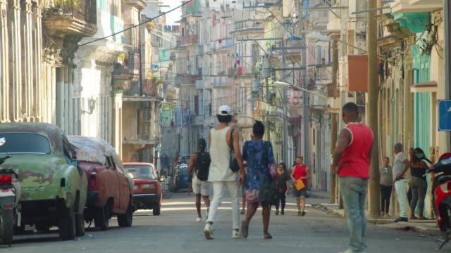 havana cuba street iconic image. people walking, old buildings and vintage car - cuban culture stock videos & royalty-free footage