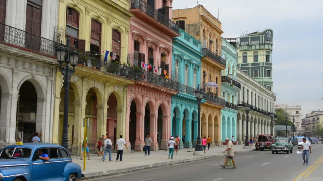 stockvideo's en b-roll-footage met havana cuba traffic of old classic autos on main street at capital with old colorful buildings and rush cars habana - cuba