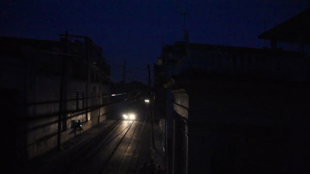 havana, cuba-circa january 2016: a black out or 'apagon' in the cuban capital city taken from a balcony in an apartment building. a car drives with... - fuel and power generation stock-videos und b-roll-filmmaterial