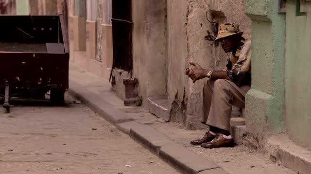 havana man sits in street - sitting点の映像素材/bロール
