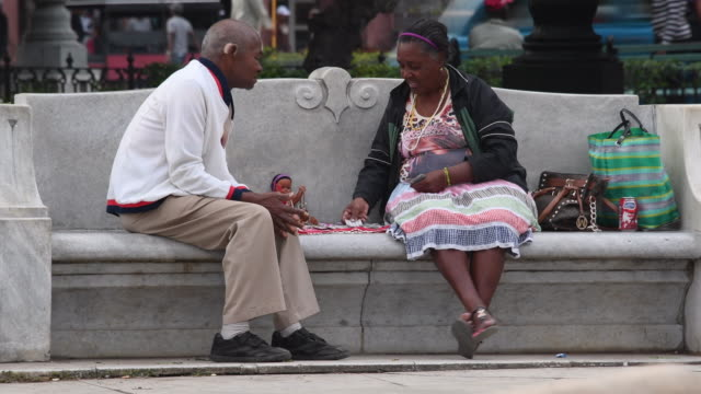 havana,cuba: afro-caribbean woman reading the cards in plaza, park or town square. - tarot cards stock videos & royalty-free footage