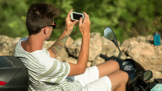 having a break - he's taking a picture (of his girlfriend) with his smart phone