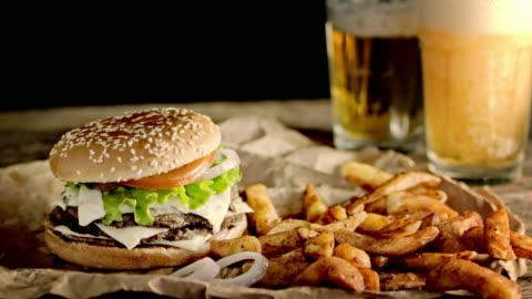 vidéos et rushes de slo mo ds ayant un hamburger double, quartiers de pommes de terre croustillantes et bière - fast food