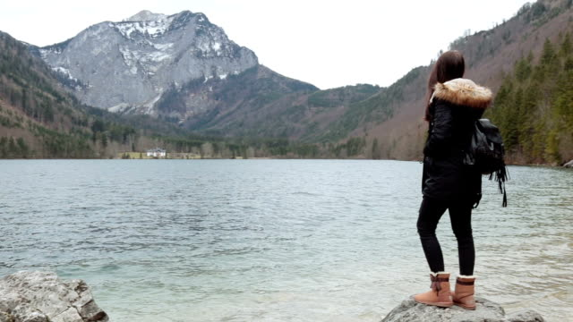 having an adventure. standing on a rock near a lake and admiring the view - upper austria stock videos & royalty-free footage