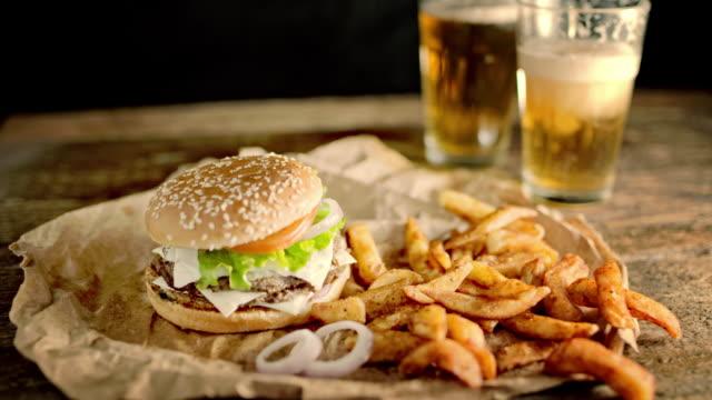 slo mo ds を持つビールとハンバーガー、カリカリ ポテト - チェダー点の映像素材/bロール
