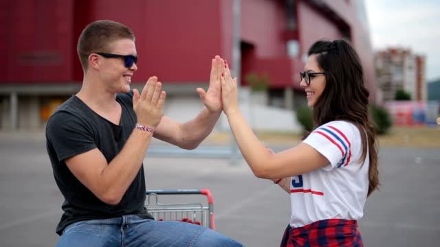 having fun on a shopping cart - coppia di giovani video stock e b–roll