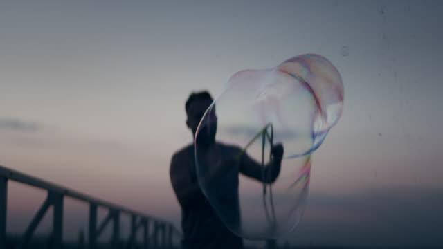 vidéos et rushes de s'amuser avec des bulles de savon. homme restant sur le toit - sans mise au point and équilibre