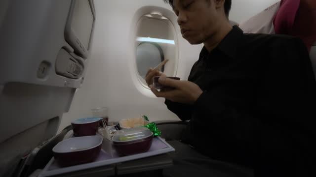 äter lunch i flygplan - mellanstor grupp av objekt bildbanksvideor och videomaterial från bakom kulisserna