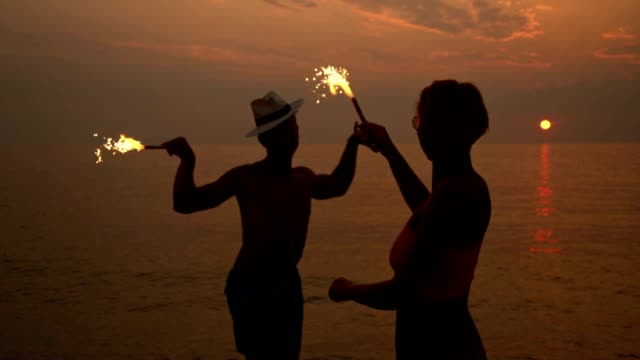 slo mo having party with sparklers on the beach - shade stock videos & royalty-free footage