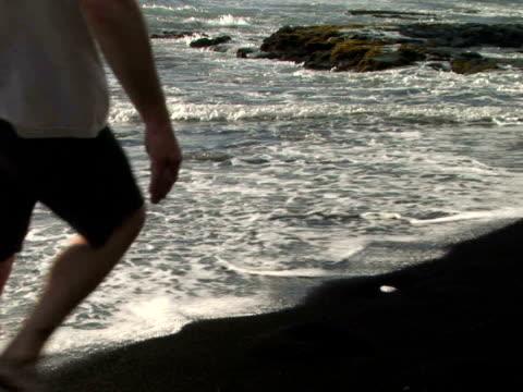 cu usa, hawaii, the big island, punaluu black sand beach park, man walking on beach, low section - black sand stock videos & royalty-free footage