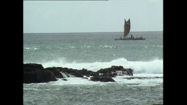 hawaiian canoe sails past rocks with breaking waves; 1983 - polynesian culture stock videos & royalty-free footage