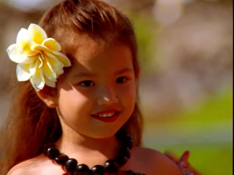 Hawaiian girl with flower in hair and beads around neck, Maui, Hawaii