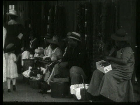 b/w hawaiian people making leis (flower necklaces) / 1919 / no sound - pazifikinsulaner stock-videos und b-roll-filmmaterial