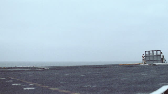 a hawkeye airplane approaches an aircraft carrier. - flugzeugträger stock-videos und b-roll-filmmaterial