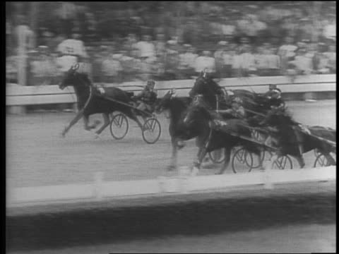 stockvideo's en b-roll-footage met hay bales stacked loft in stable / man working on cart wheel with horse looking at him through window / panning high angle view of harness race /... - 1942