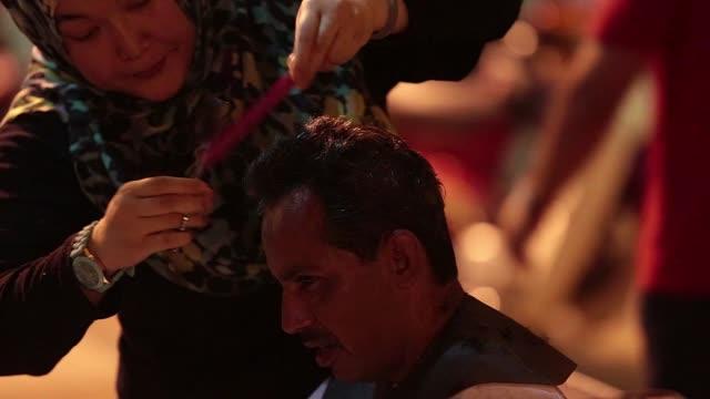 hay que cuidar la autoestima ademas de comida y atencion medica en un comedor social de kuala lumpur los mas desfavorecidos pueden cortarse el pelo... - comida stock videos & royalty-free footage
