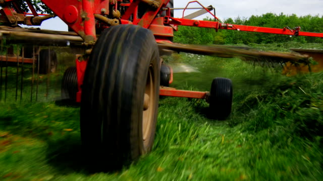 stockvideo's en b-roll-footage met gimbal haymaking in spring with tedder pov (4k/uhd to hd) - tractor