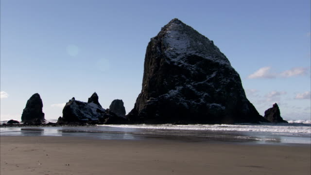 haystack rock and smaller rock formations outline a blue sky at cannon beach, oregon. available in hd. - cannon beach stock videos & royalty-free footage