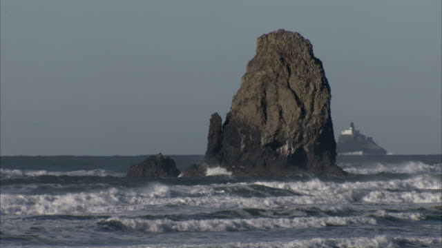 haystack rock juts above the pacific ocean near an offshore lighthouse. available in hd. - oregon coast stock videos and b-roll footage