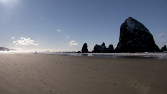 haystack rock towers over other rock formations on cannon beach along the oregon coast. available in hd. - cannon beach stock videos & royalty-free footage
