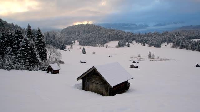 haystead with frozen lake geroldsee on morning in winter, gerold, garmisch-partenkirchen upper bavaria, bavaria, germany, european alps - garmisch partenkirchen stock videos and b-roll footage