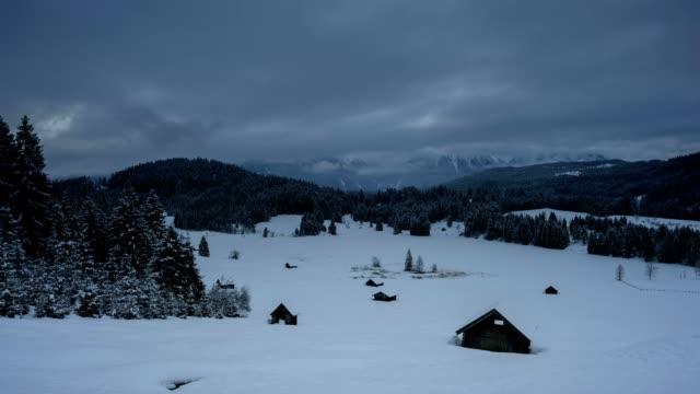 vídeos de stock, filmes e b-roll de haystead with frozen lake geroldsee on morning in winter, gerold, garmisch-partenkirchen upper bavaria, bavaria, germany, european alps - alta baviera
